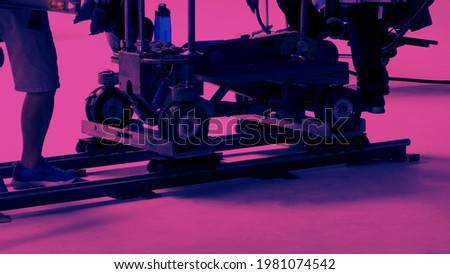 Dolly track setting up by film crew man. Behind the scene of video production crew setting dolly track in studio with professional equipment. Set up for shooting vdo production. film industry concept Stock photo ©