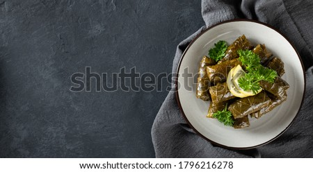 Dolma - stuffed grape leaves with rice and meat on a dark background, view from above, copy space. Traditional Greek, Caucasian and Turkish cuisine Stock photo ©
