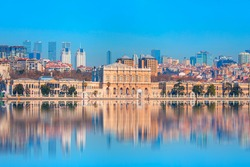 Dolmabahce Palace (Dolmabahce Sarayi) seen from the Bosphorus - Dolmabahce palace against coastal cityscape with modern buildings - Istanbul, Turkey