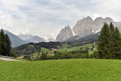 Dolomites alpine mountains landscape. Green meadow on front side of picture and mountains peaks on the background. Dolomity, Italy.Famous landmark.Travelling concept background.