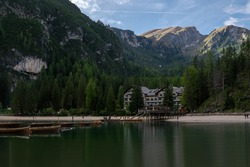 Dolomites Alps. Lake Braies. Italy. resort hotel at the foot of the mountains by the lake with shipyard and boats on the water in the shadow of pine forest. Blue sky in the summer sunny day