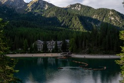 Dolomites Alps. Lake Braies (Lago di Braies, Wildsee). Italy. resort hotel at the foot of the mountains by the lake with shipyard and boats on the water in the pine forest in the summer