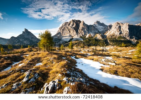 Dolomiti peaks and meadow with first autumn snow