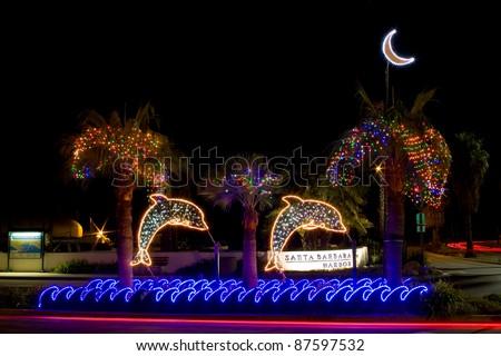 Dolphin Christmas light decorations light the entrance to Santa Barbara harbor at night.