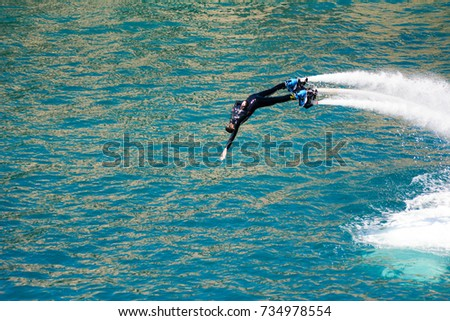 dolphin style during a flyboard show in the ionian sea on blur background
