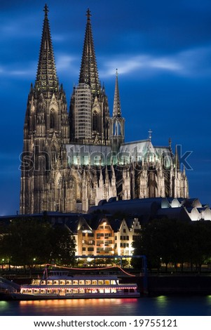 Dom in Cologne with boat on the river Rhine at sunset lighting.