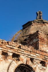 Dome and arch on an ancient ruined and abandoned building, blurred blue sky.