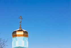 Dome of a rural Orthodox cathedral with a cross against a clear blue sky. Simple village church. Selective focus.