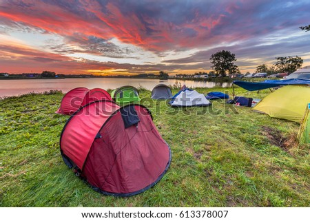 Dome tents camping near lake on a music festival camp site under beautiful sunrise
