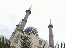 domes and minarets of the mosque with the inscription of Allah on the front of the building against a foreground of leaves