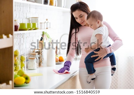 Domestic chores at maternity leave. Young mother with baby boy cleaning kitchen at home, free space