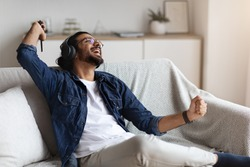 Domestic Fun. Cheerful Western Guy Listening Music In Headphones And Dancing At Home, Joyful Young Indian Man Sitting On Couch And Enjoying His Favorite Playlist On Smartphone, Chilling In Living Room