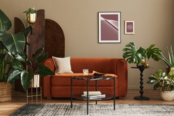 Domestic interior of living room with design sofa, mock up poster frames, a lot of plants, coffee table, room screen and elegant personal accessoreis in modern home decor. Template.