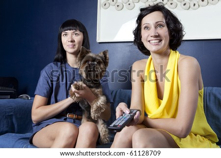 domestic life: 2 girls in dress and dog watching a comedy movie