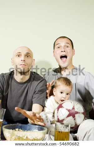 Domestic life: Two young men and little boy watching a football match on tv