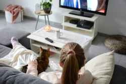 Domestic life with pet at home. A young woman is sitting on the couch with her cat on her lap in the living room. She watches TV while stroking her cat. Binge watching tv via online streaming platform