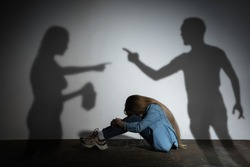 Domestic physical violence, abusing. Scared little caucasian girl, victim sitting close to white wall with shadow of angry threatening parents with alcohol addiction. Awareness of social problem.
