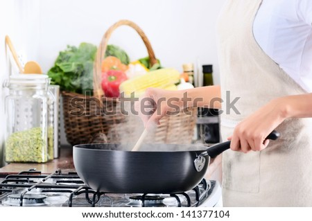 Domestic scene of anonymous woman cooking by the gas stove with a steaming pot