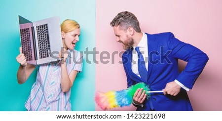 Domestic stress. Family couple. Husband stand with dust brush while wife holding laptop. Businessman and housewife. Couple of handsome man and pretty woman. Housekeeping or business. #1423221698