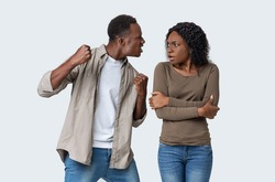 Domestic violence and abuse concept. Young african american mad man threatening his woman with his fist, gray studio background. Furious black guy showing fists his scared girlfriend or wife