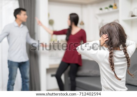 Domestic violence and Family conflict concept. Sadness little girl against blured of mother fighting father with quarrel at home. Setup studio shooting. Stock photo ©