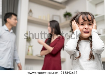 Domestic violence and Family conflict concept. Sadness little girl against blured of mother fighting father with quarrel at home. Stock photo ©