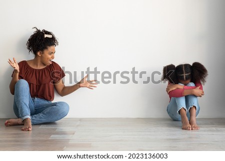 Domestic violence, kids abuse at home concept. Mad black lady abusive mother emotionally gesturing and shouting at her crying female kid, sitting together on floor over empty wall, copy space Photo stock ©