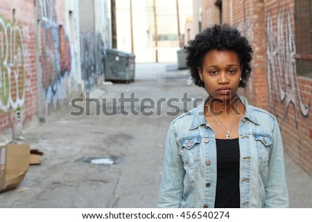 Domestic violence, portrait of abused and hurt young woman showing sadness outdoors with copy space