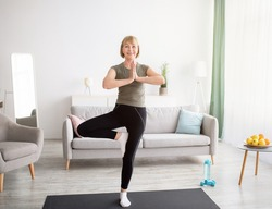 Domestic yoga practice. Positive mature lady standing in tree pose, keeping balanced during covid lockdown at home. Happy senior lady in sportswear exercising indoors, copy space