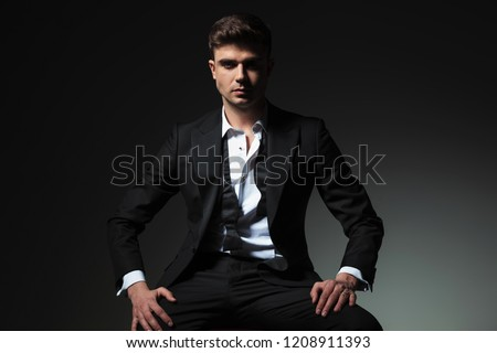 dominant man in black tuxedo with open collar and undone bowtie sitting on grey background with hands on thighs Stock photo ©
