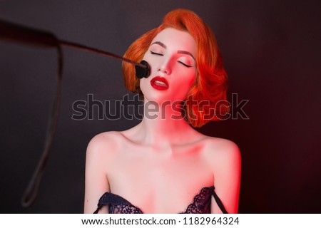 Dominant with a whip in hand. Attire for bdsm games. Redhead girl feel pleasure. Kinky model with stack on face. Bdsm toy for fetish. Man dominant. Cunning woman seduction. Perverse sexual pleasure #1182964324