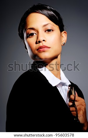 Domineering woman in business suit holding to a pair of glasses, with dramatic lighting
