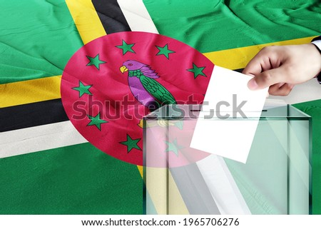 dominica flag, dominica  the symbol of elections Male hand puts down a white sheet of paper with a mark as a symbol of a ballot paper against the background   Stockfoto ©