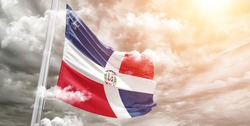 Dominican Republic national flag cloth fabric waving on beautiful grey sky.