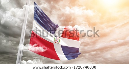 Dominican Republic national flag cloth fabric waving on beautiful grey sky. Foto stock ©