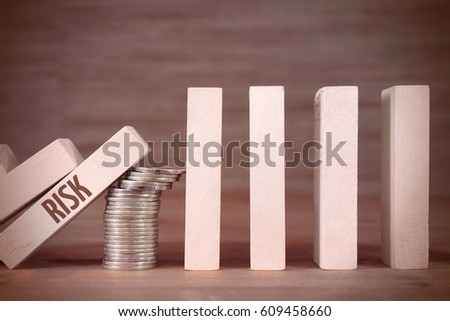 Domino effect and a column of coins and inscription Risk #609458660