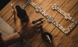 Domino game at home, detail of a man's hand, with a cigarette between his fingers and with multiple rings, on the table there are dominoes, beer bottles and cigars.