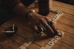 Domino game at home, detail of a man's hand, with multiple rings and putting a chip in the game, on the table there are domino chips, beer bottles and cigars.