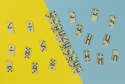 domino game concept, tiles organized in even and odd on the two-tone yellow and light blue surface, top view