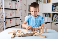 Domino pieces lined up by the hand of a 6 year old boy, boy builds a line of wooden dominoes