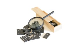 Dominoes and magnifying glass. Wooden box  with chips. Risk study concept. Isolated over white background.