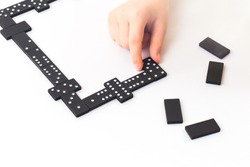 Dominoes game. Kids hand is holding a domino tile with some on table. Boardgame concept