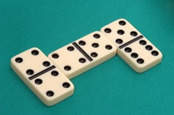 Dominoes game on green fabric  background