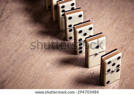 Dominoes standing in a row on a wooden table