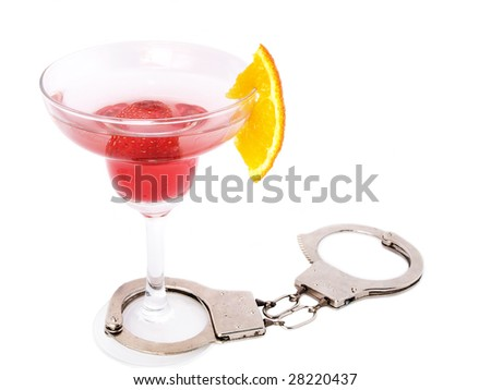 Don't drink and drive concept - cocktail glass with handcuffs - stock photo