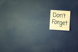 don't forget reminder, written on sticky memo attached to blackboard