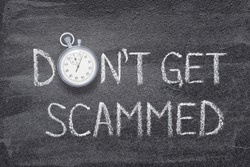 don't get scammed phrase written on chalkboard with vintage precise stopwatch