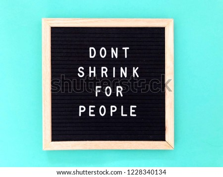 Don't shrink for people. Motivational quote on black message board. Turquoise background.
