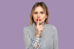 Don't speak! Serious teacher in striped blouse looking angrily and holding finger on red lips, gesturing shut up, stop talking in class and stay quiet. indoor studio shot isolated on purple background