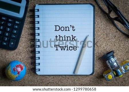 DON'T THINK TWICE inscription written on book with globe,eyeglasses, calculator, camera, pencil and vase on wooden background with selective focus and crop fragment. Business and education concept Stock fotó ©
